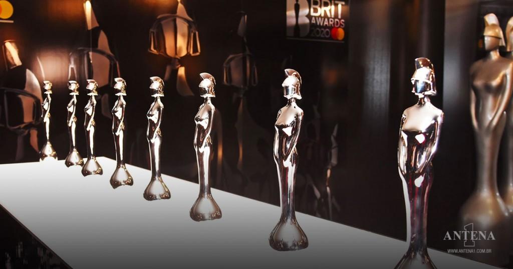Placeholder - loading - Estatuetas do BRIT Awards em fundo característico