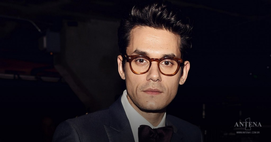 Placeholder - loading - John Mayer usando terno e óculos com armação redonda olhando para câmera em fundo escuro – Photoshoot/Divulgação