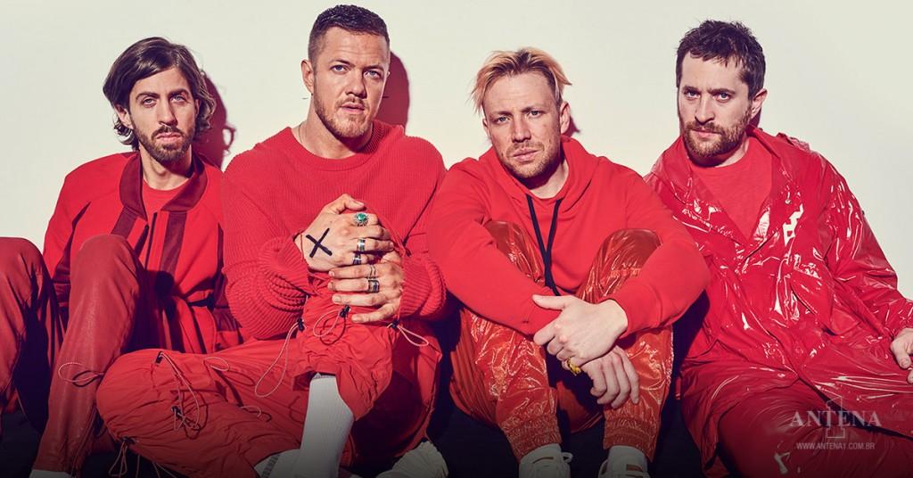 Placeholder - loading - Imagine Dragons – Da esquerda para direita: Daniel Wayne Sermon, Dan Reynolds, Ben McKee e Dan Platzman. Banda usa macacões vermelhos encostados em parede branca – Photoshoot/Divulgação