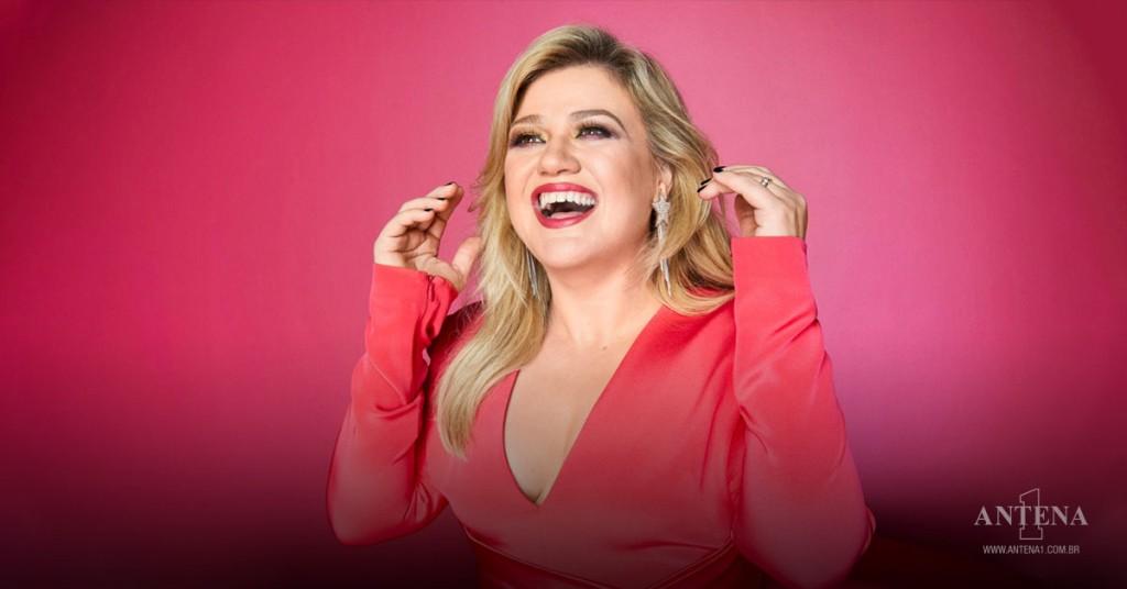 Placeholder - loading - Kelly Clarkson em fundo vermelho