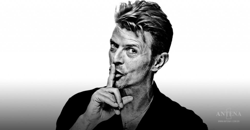 """Placeholder - loading - David Bowie: Artista em preto e branco fazendo o sinal de """"quieto"""" com o dedo indicador na boca olhando para câmera - Photoshoot/Divulgação"""