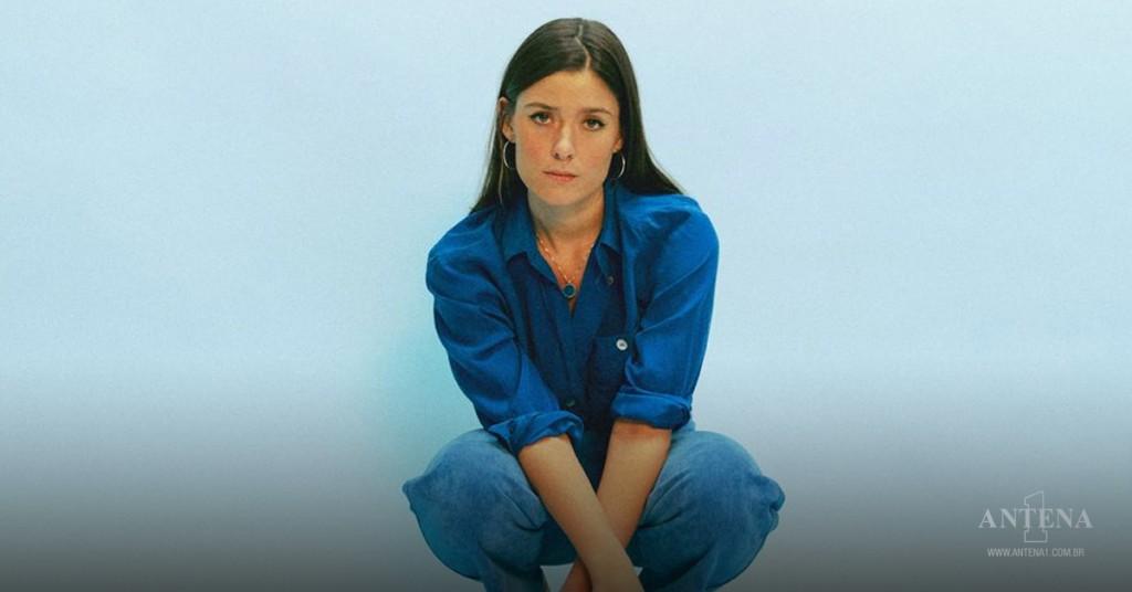 Placeholder - loading - Léon – cantora usando roupas azuis escuras em um fundo azul claro – foto/Divulgação