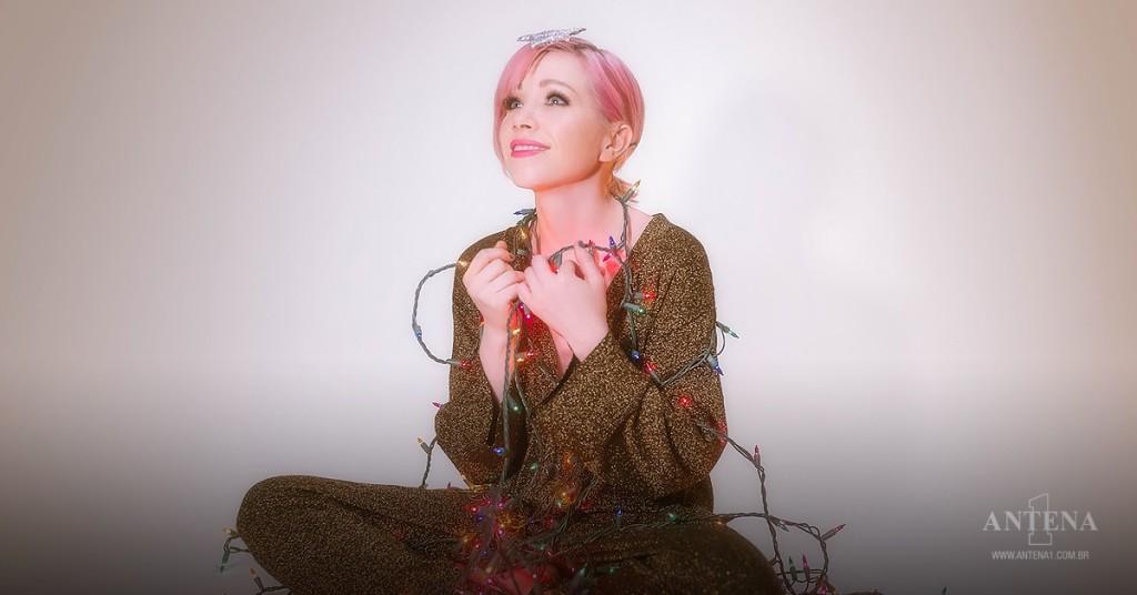 Placeholder - loading - Carly Rae Jepsen olhando para cima com um pisca-pisca ao redor do corpo e uma estrela de plástico na cabeça – Foto tirada de videoclipe oficial/Divulgação