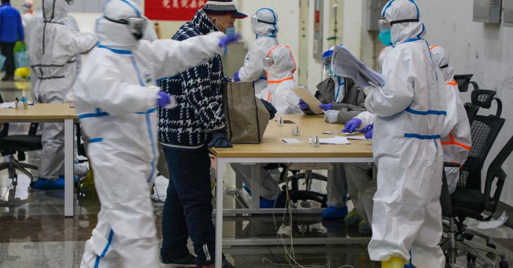 Placeholder - loading - Vestidos com trajes especiais, médicos atendem paciente em hospital provisório montado em Wuhan, na província de Hubei, para tratamento de coronavírus  05/02/2020 China Daily via REUTERS