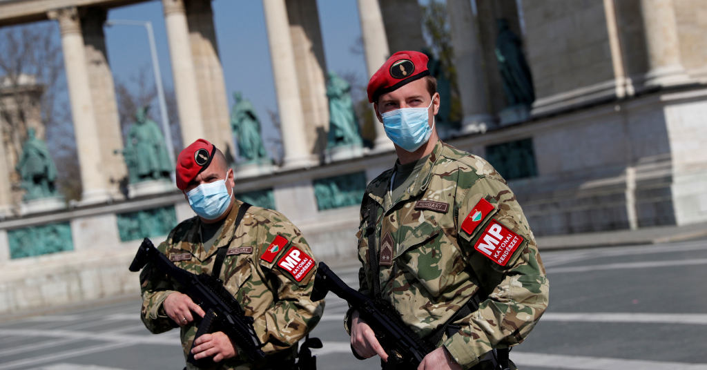Placeholder - loading - Agentes de segurança em praça deserta de Budapeste 06/04/2020 REUTERS/Bernadett Szabo