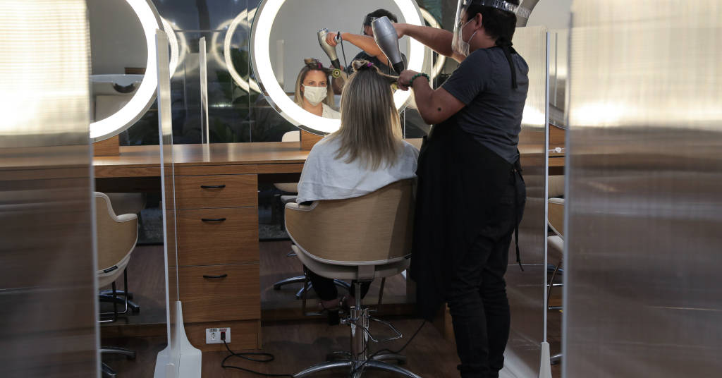 Placeholder - loading - A hairdresser wearing protective mask and face shield uses a hair dryer on a customer's hair between acrylic walls set up for social distancing at a hair salon, as the city eases the restrictions impo