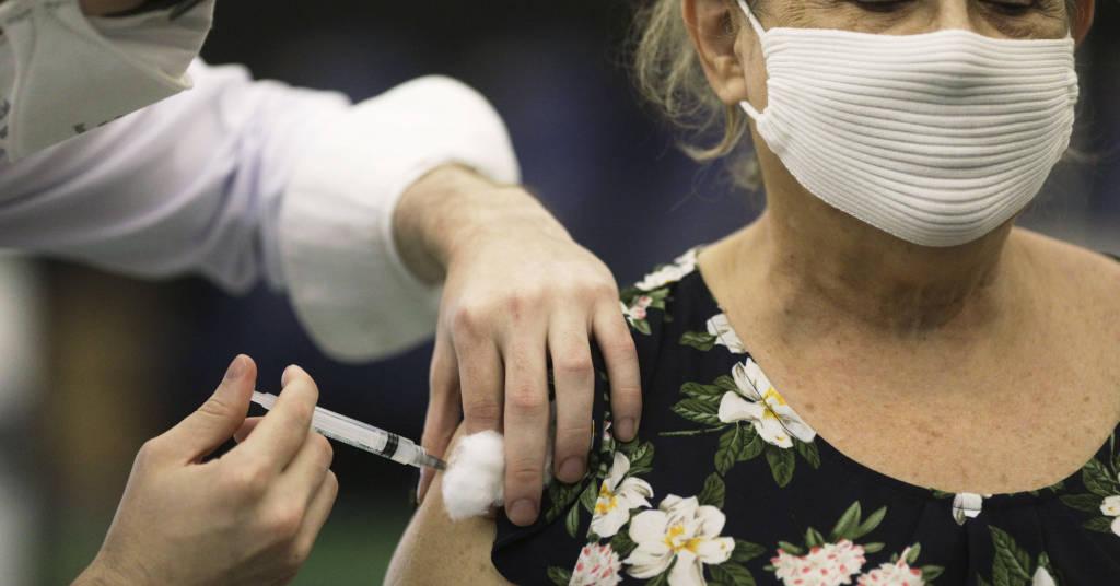 Placeholder - loading - Mulher é vacina contra a Covid-19 no Rio de Janeiro. 18/03/2021. REUTERS/Ricardo Moraes.