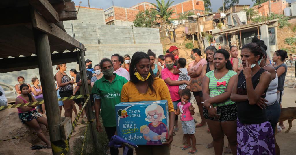 Placeholder - loading - Mulher carrega caixa de doações de alimentos na favela da Capadócia, em São Paulo 01/05/2020 REUTERS/Amanda Perobelli