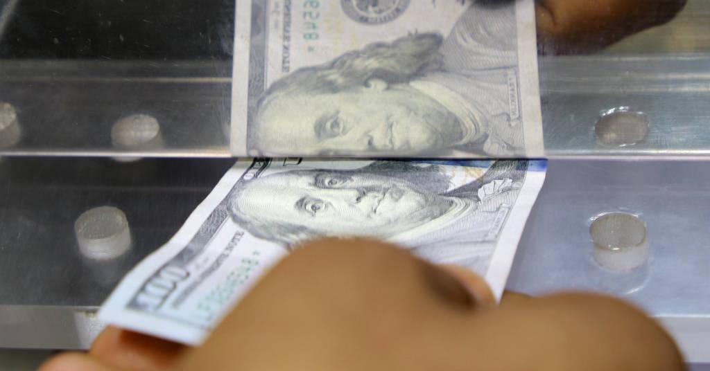 Placeholder - loading - Pessoa entrega nota de dólar dos EUA em casa de câmbio em Aden, Iêmen  29/06/2021 REUTERS/Fawaz Salman