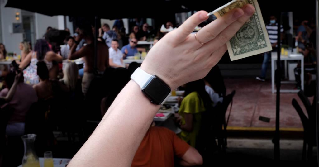 Placeholder - loading - Homem segura uma nota de dólar em bar em Miami Beach, Flórida, EUA 06/03/2021 REUTERS/Marco Bello