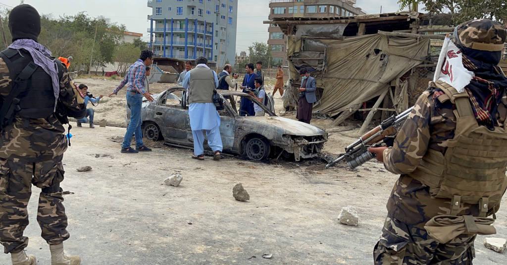 Placeholder - loading - Afegãos tiram foto de veículo de onde foram lançados foguetes, observados por combatentes do Taiban 30/08/2021 REUTER/Stringer