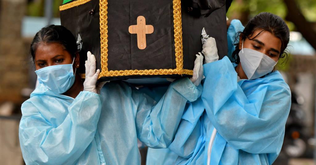 Placeholder - loading - Voluntários Akshaya (D), 22, e Esther Mary, 41, carregando um caixão com corpo de vítima de Covid-19 em Bengaluru, Índia 18/5/2021 REUTERS/Samuel Rajkumar