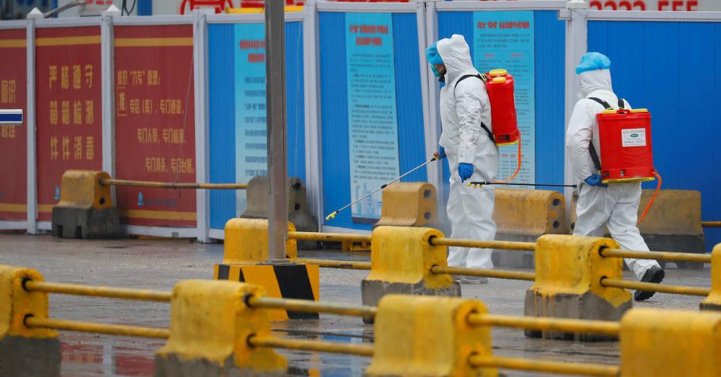 Placeholder - loading - Trabalhadores lançam desinfetante em mercado de Wuhan durante visita da OMS 31/01/2021 REUTERS/Thomas Peter