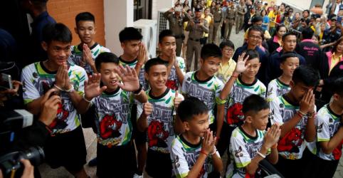 Meninos tailandeses sorriem e acenam em 1ª aparição pública após resgate