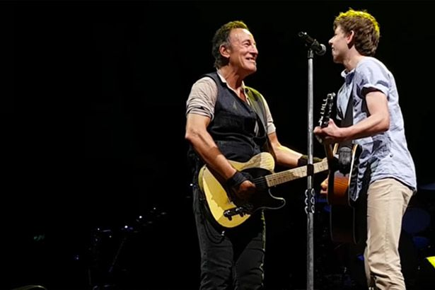 Bruce Springsteen toca com fã no palco Background